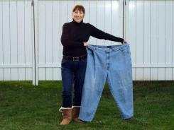 Elaine Jacobson holds up a pair of her old jeans at her Rochester, N.Y., home.