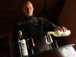 Warren McLellan pours a glass of grape juice at Oakencroft Farm in Charlottesville, VA,