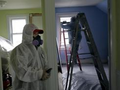 Luis Benitez, foreground, and Jose Diaz, background, clean up lead paint in a contaminated building.