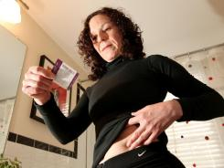 Kathryn DiPasqua, 51, reads the label of her Vivelle dot (.025) mg patch which she applies once a week.