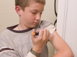 Nicholas Rudd, age 10, demonstrates how he would give himself an insulin shot using the door of a refrigerator to prop up his arm to be able to inject insulin in the proper place.