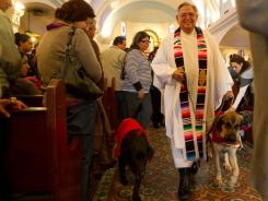 Clerical canines: Father Roy Snipes of Our Lady of Guadalupe Catholic Church in Mission, Texas, with Chunkly, left, Puebla and Bendito, all in vestments.