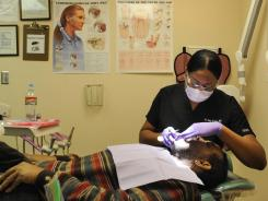 Dr. India Gibson works with patient Alford Harris at the David Raines Dental Clinic in Bossier City, La.. Harris was in to adjust his new dentures.