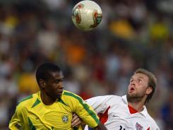 U.S. forward Clint Mathis  and Brazilian defender Juan jump to head of f the ball during their soccer Confederations Cup match.