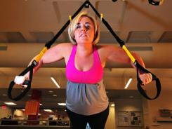 Jaclyn Sanderson exercises on a training system that uses the body's weight for an intense workout.