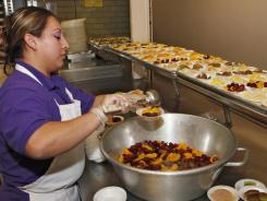 Vivan Perez prepares bowls of fruit for lunch in the kitchen at Kepner Middle School in Denver.