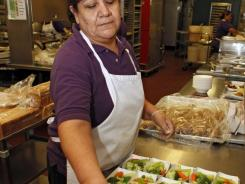 In this Jan. 18, 2012 photo, Maria Salas prepares salads for lunch in the kitchen at Kepner Middle School in Denver.