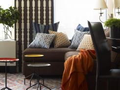 In this image released by Brian Patrick Flynn Designs, a room designed by Brian Patrick Flynn, includes: The living room with several layers of pattern -- from the zig-zag floors, baluster wallpaper and graphic pillows -- to add visual depth.
