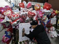 A man photographs a card at a memorial to Whitney Houston outside New Hope Baptist Church in Newark, N.J., on Friday.