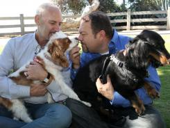 Steven May, left, holding his dog, Winnie, sitting with his attorney, David Pisarra, holding his dog, Dudley.