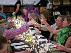 Diners toast between courses during a Mardi Gras-themed L.I.M.E. evening at the Charleston Library Society.