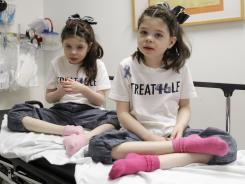 Hempel, 6, at left ,and her twin sister Cassidy await treatment at the Children's Hospital and Research Center in Oakland, Calif., Friday, March 18, 2011. The Hempel twins are receiving alternative treatment for Niemann Pick Type C disease, a rare disorder where harmful amounts of cholesterol accumulates in vital organs.