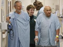 Bob Landorf, left, and Anthony Pazzur walk the corridors with volunteer Barb Diedrich at Northwest Community Hospital in Arlington Heights, Ill. Northwest Community has a new program that pairs patients with hospital volunteers, who get patients up out of bed and moving, and also act as buddies, giving people someone to talk to, and lift their spirits.