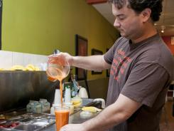 Animo Juice co-owner Anthony Gentleski pours an Animo Glow at the store in Haddonfield, N.J.