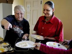 Susan Adams, left, a volunteer, serves food to Celeste Salcido, right, a client of The Crossroads, and other clients after a group meeting. Crossroads for Women is an Albuquerque organization that provides housing, counseling and support services to women who have experienced abuse, addictions, homelessness and incarceration.