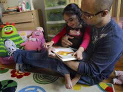 Christopher Astacio reads with his daughter Cristina, 2, recently diagnosed with a mild form of autism. Autism cases are on the rise again, largely due to wider screening and better diagnosis, federal health officials said.