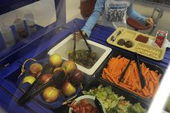 Children pick fruits and vegetables including locally grown carrots and apples at a Massachusetts school.