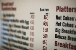 Calories of each food item appear on a drive-thru menu in New York.