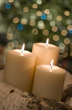 Holiday candles in front of Christmas tree.