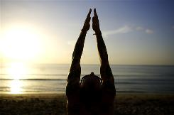 Jesse Albrecht of Cedar Rapids, Iowa, and other yoga practitioners from around the world do sun salutations and silent meditations on the beach at sunrise in Fort Lauderdale, Fla.