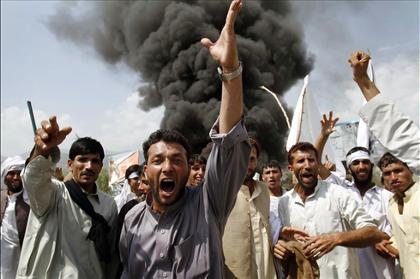 Afghans in Jalalabad, east of Kabul, shout anti-U.S. slogans Friday as they burn tires and block a highway during a protest in reaction to a small American church's plan to burn copies of the Quran.