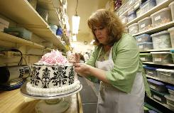 Suzi Finer, a cake decorator at Hansen's Cakes in Beverly Hills, writes several status updates a day on Facebook and Twitter about what's going on with her work and other things.