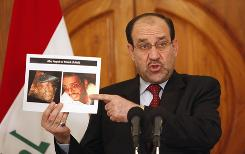 Iraq's Prime Minister Nouri al-Maliki holds photographs of a man  the Iraqi government says is al-Qaeda leader Abu Ayyub al-Masri at a  news conference in Baghdad.
